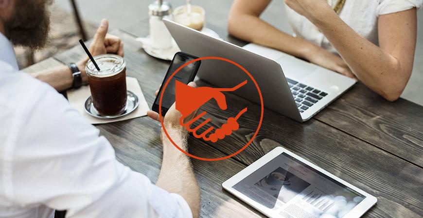 Tisch mit zwei Personen und Laptop, Tablet und Glas
