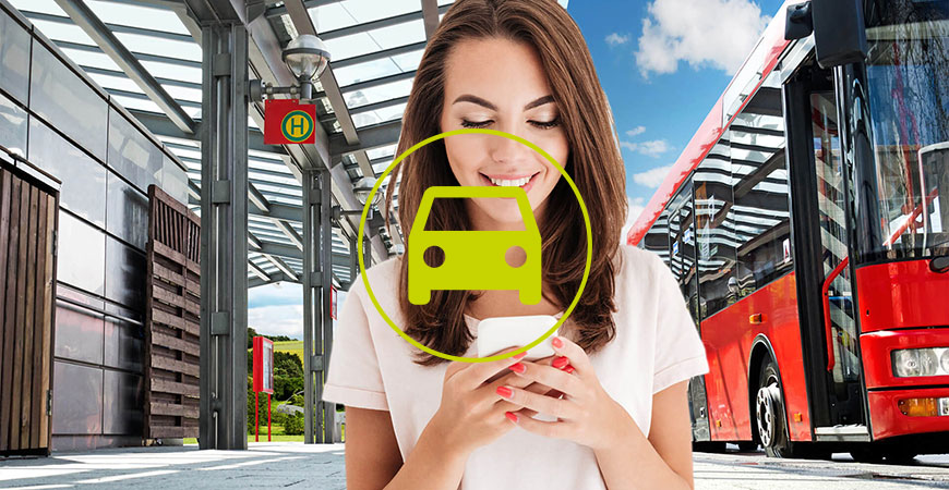Frau schaut an Busshaltestelle aufs Handy