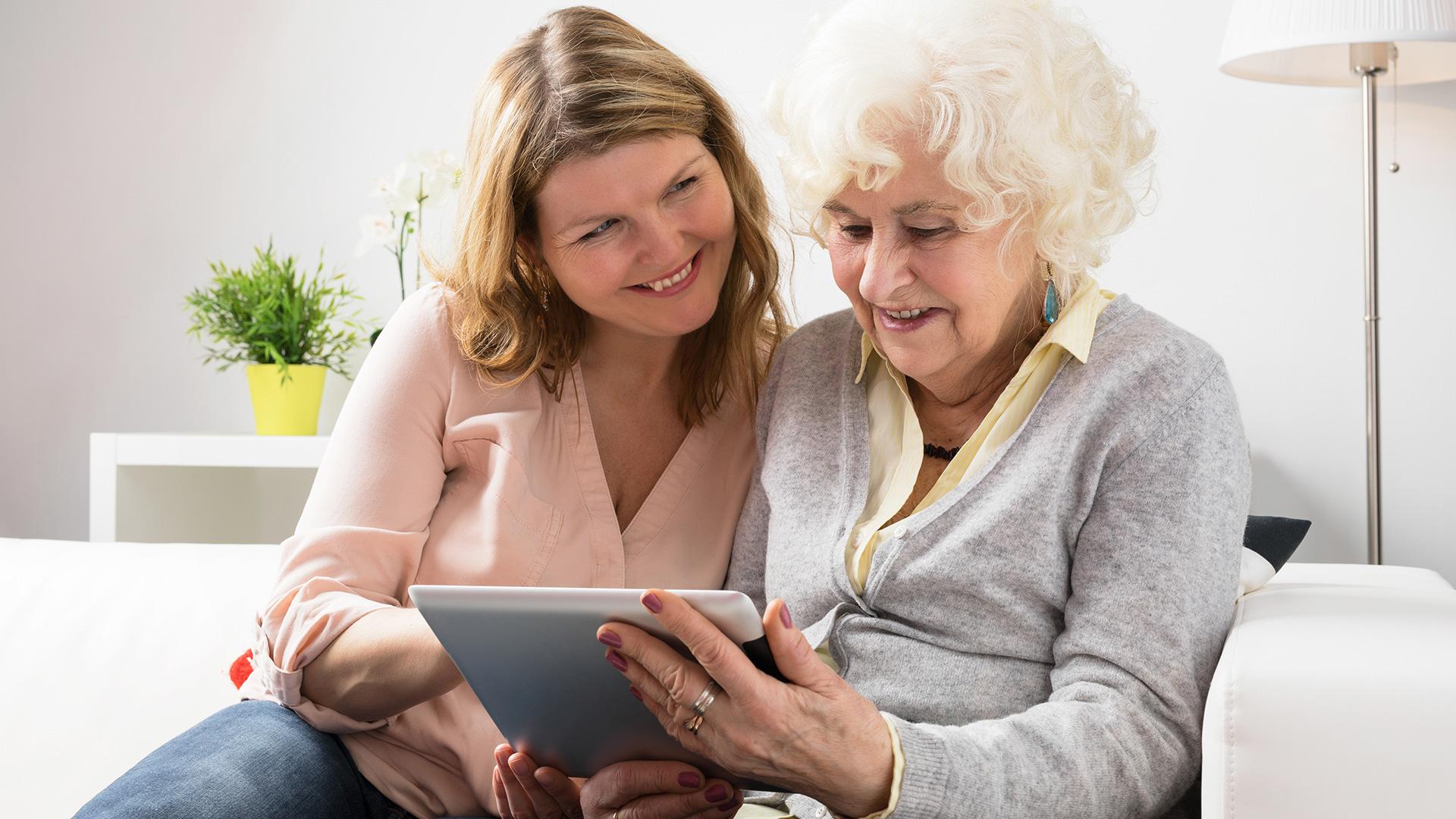 Junge und alte Frau mit Tablet