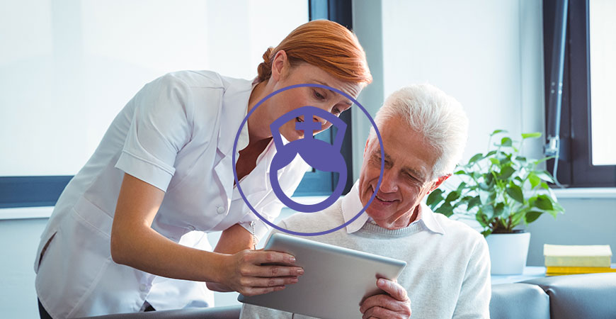 Pflegekraft erklärt älteren Herren ein Tablet