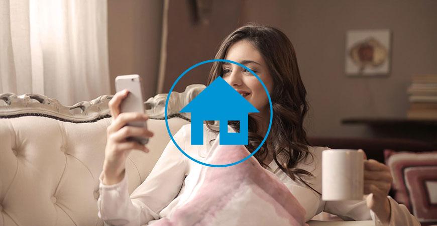 Frau auf Sofa mit Handy und Kaffeetasse
